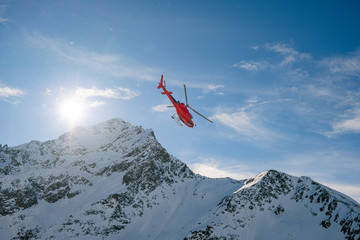 Red rescue helicopter flying over the view of the snowy rocks in Alpine ski resort Zermatt near Matterhorn mountain. Winter nature landscape of Swiss Alps. Mountains with snow in Switzerland.