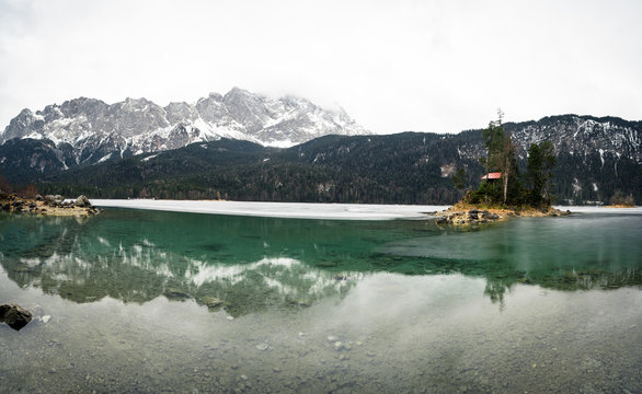 Beautiful winter day at the Eibsee near grainau at the mountain zugspitze, reflection of island Braxeninsel in the winter
