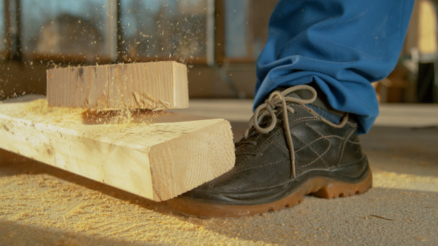 CLOSE UP: Detailed shot of painful work accident as plank falls on worker's foot