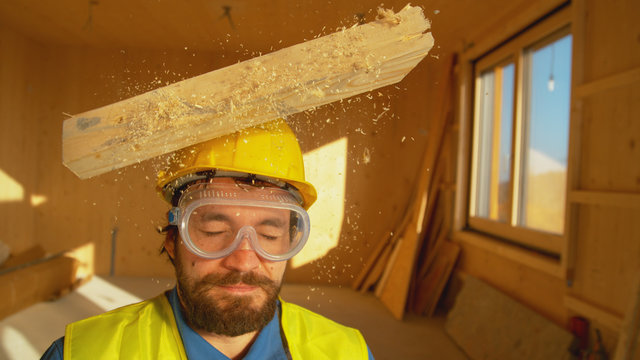 PORTRAIT, CLOSE UP: Wooden board falls on an unsuspecting builder's head.