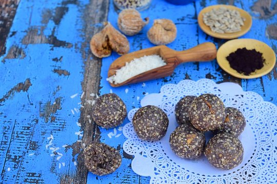 Vegan energy balls with Maqui berry powder, acai powder, quinoa, fig, sunflower seed and coconut flakes on doily paper
