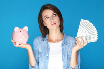 Young woman holding dollar banknotes and piggybank on blue background