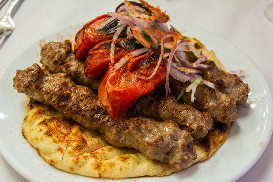 Greek souvlaki kebap with grilled tomatoes, on a pita bread.