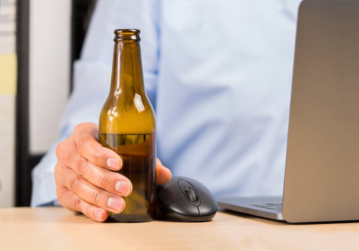 and of a businessman in the office drinking a bottle of beer