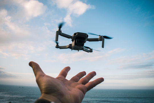 Pequeño dron despegando desde una mano en un día soleado