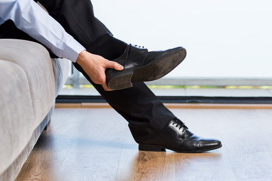 businessman taking off shoes after work at home