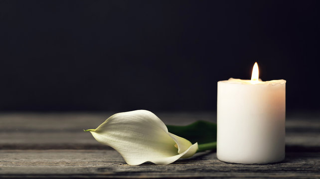 Burning candle and white calla lily on dark background with copy space. Sympathy card