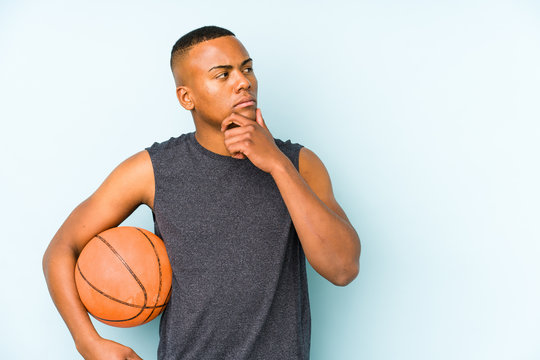Young colombian man playing basketball isolated looking sideways with doubtful and skeptical expression.