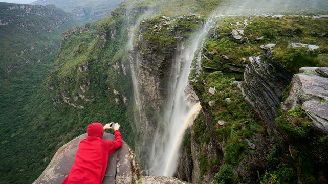 Traveler lies on the edge of the cliff and taking a picture of the waterfall in Chapada Diamantina national park, State of Bahia, Brazil.