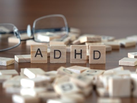 the acronym adhd for Attention deficit hyperactivity disorder concept represented by wooden letter tiles on a wooden table with glasses and a book