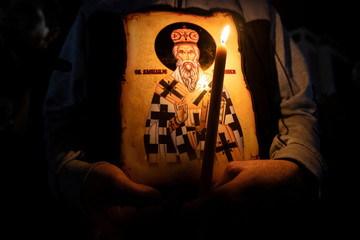 A kid holds a candle and an icon during a protest march against a new law on religious freedom and legal rights of religious organizations in Podgorica