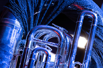 A tuba with a cloth on top of it in blue stage lights