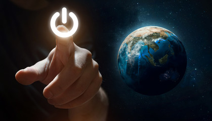 Hand press Power Button near Earth planet. Earth hour event. Protection of environment. Elements of this image furnished by NASA