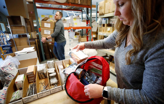 Kristen Curley, owner of Nitro-Pak, puts items into a backpack as part of personal protection and survival equipment kits ordered by customers preparing against novel coronavirus, at Nitro-Pak in Midway