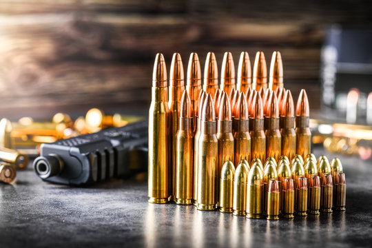 Various kind of bullets or ammonution on dark stone table. Bullet pile in war ammo background. Magazines, rounds and military technology. Banner or panorama guns photo..