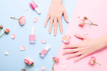 Beautiful woman manicure on creative trendy pink and blue background.