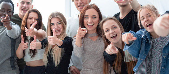 group of smiling young people pointing at one point