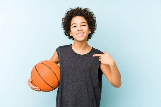 Kid boy playing basketball isolated on blue background person pointing by hand to a shirt copy space, proud and confident