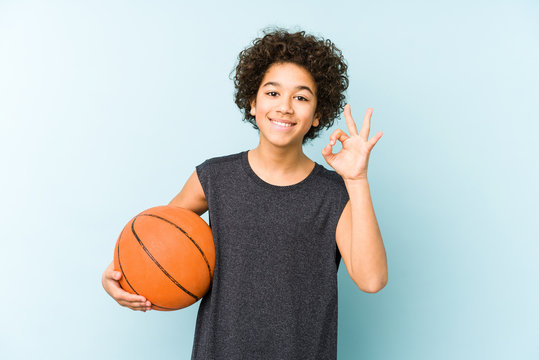 Kid boy playing basketball isolated on blue background cheerful and confident showing ok gesture.