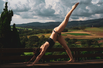 Sporty young woman doing stretching while exercise, balance posture. Beautiful athletic girl practicing yoga against the backdrop of beautiful nature.
