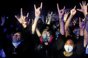 Fans wearing protective masks enjoy a band's performance at Hidden Agenda: This Town Needs (TTN) Live House during the club's last concert as business plummets due to the fear of the coronavirus, in Hong Kong