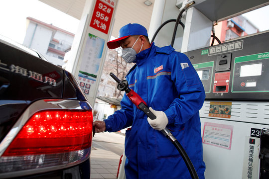 A pump attendant wears a mask as he refuels a car at a Sinopec gas station where customers can buy supplies in Beijing
