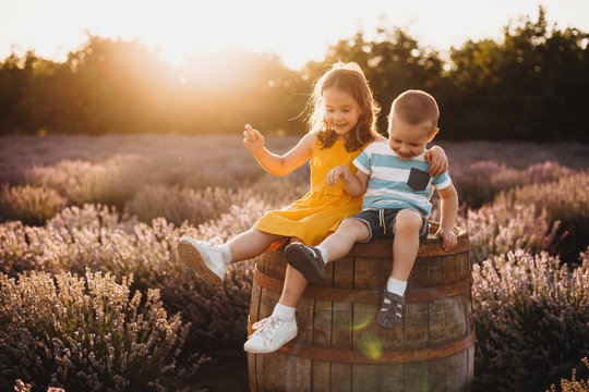 Caucasian boy having joy with his bigger sister sitting on a barrel with a lavender field on background