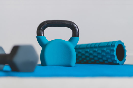 home gym concept, blue yoga mat with kettlebell foam roller and dumbbell shot at shallow depth of field from low perspective