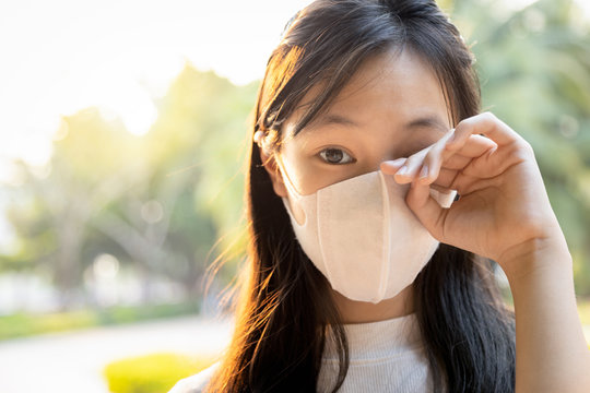 Asian child girl wearing protective mask,people rubbing the eyes due to air pollution,fine dust entering the eye,unclean hand,dirty hands,touch her eyes,risk of infection from spread of Covid-19 virus