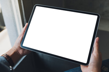 Mockup image of a woman holding black tablet pc with blank white screen in cafe - fototapety na wymiar