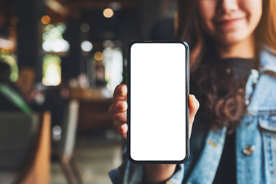 Mockup image of a woman holding and showing black mobile phone with blank white screen in cafe
