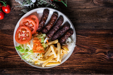 Spicy kofte (cevapcici, grilled minced meat) served with fresh tomatoes, lettuce, salad, vegetables and French fries on a rustic wooden board