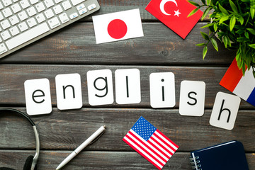 Learn English online. Concept with text, headset and keyboard on dark wooden background top-down