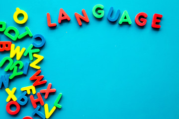Learn foreign language. Concept with letters on blue background top-down copy space