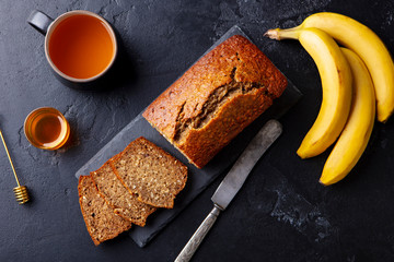Banana, coconut bread, cake with cup of tea on slate board. Dark stone background. Copy space. Top view.