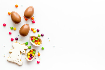 Sweet Easter symbols - chocolate eggs and bunny gingerbread - on white background top-down frame copy space