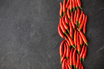 cooking, food and culinary concept - red chili or cayenne pepper on slate stone surface