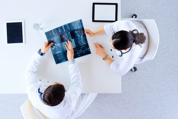 Doctor or surgeon with spine x-ray and clipboards at hospital, medicine, healthcare and surgery concept