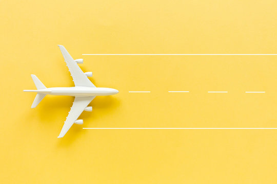 Model white plane, airplane on yellow background. Top view, flat lay. Travel, vacation concept.