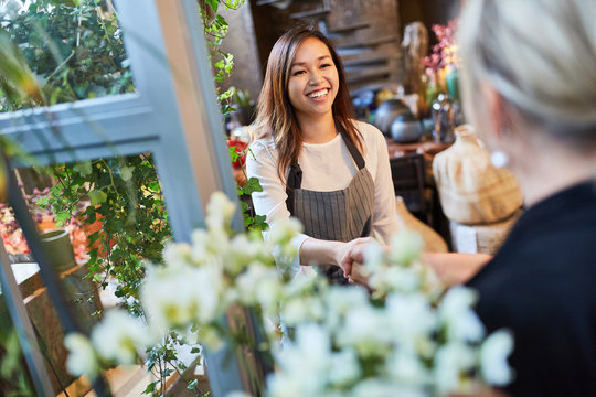 Florist welcomes customer with handshake in flower shop