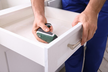 Worker installing kitchen furniture with electric screwdriver, closeup Wall mural