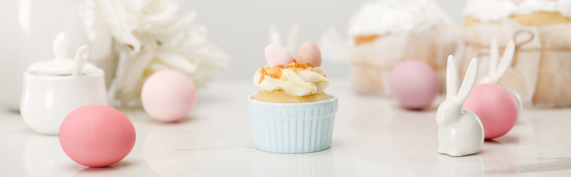 Selective focus of cupcake with colorful chicken eggs, decorative bunnies and sugar bowl on white background, panoramic shot