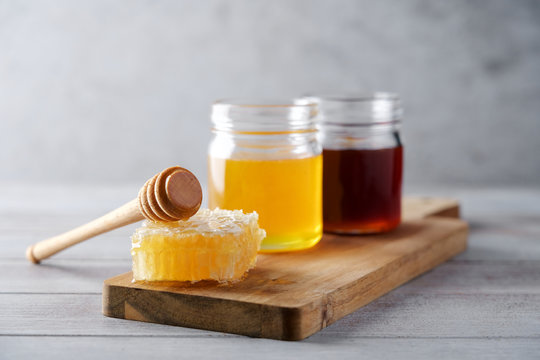 Fresh honey and honeycombs on wooden cutting board. Light floral and dark honey in glass jars