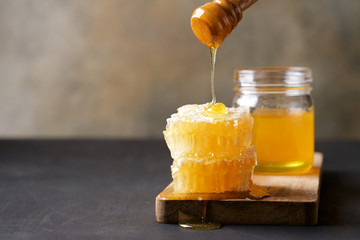 Fresh honey and honeycombs on wooden cutting board. Light floral honey in glass jars