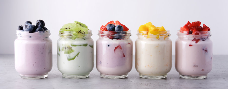 Variety of yogurts in glass jars. Healthy Breakfast Concept. Banner Photography