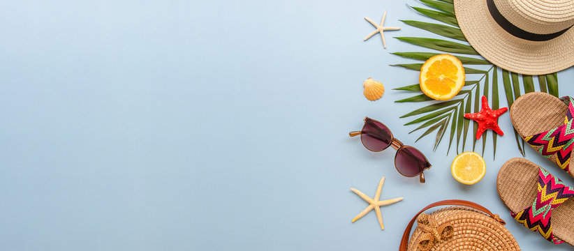 Top view summer banner with palm leaves and female beach accessories on a blue background. Rattan bag, sunglasses, hat and flip flops with copy space