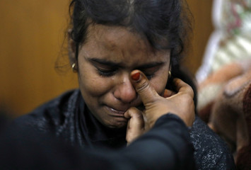 A Muslim girl is consoled in a shelter camp after she and her family fled their home following clashes between people demonstrating for and against a new citizenship law in a riot affected area in New Delhi
