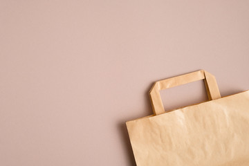 Empty kraft paper bag on brown background with copy space. Packaging template mockup