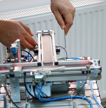 Closeup of male technician repairing automation system's electronic card by allen key.