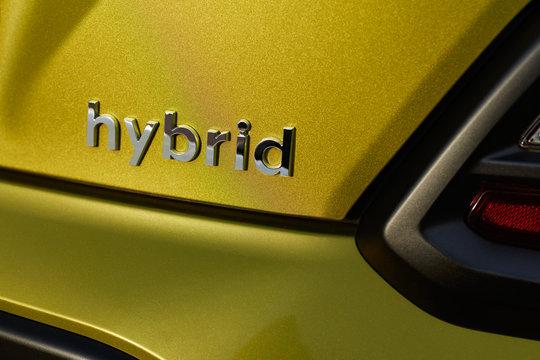 Chromed hybrid car logo on green background